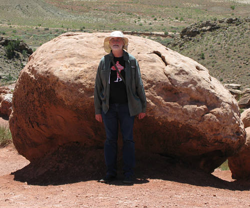 Mark leaning against a big red rock