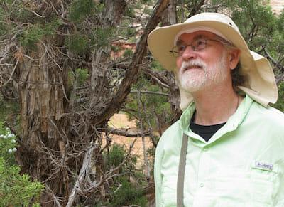 Mark gazing hopefully and surrounded by trees